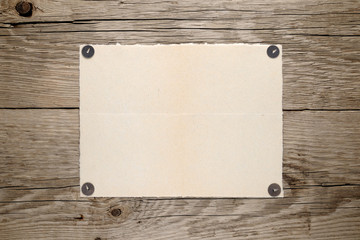 Old paper pinned to wooden wall