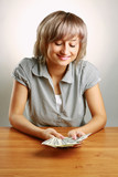 A young woman holding dollars, isolated on grey