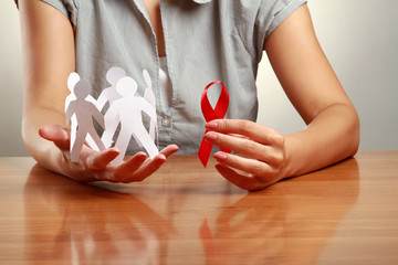 A woman holding paper peolple and an aids red ribbon
