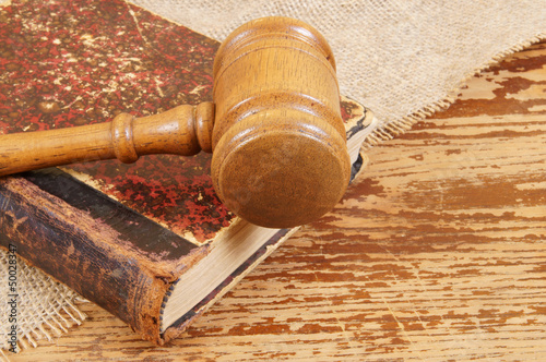 Judge's gavel and very old legal book on wooden background