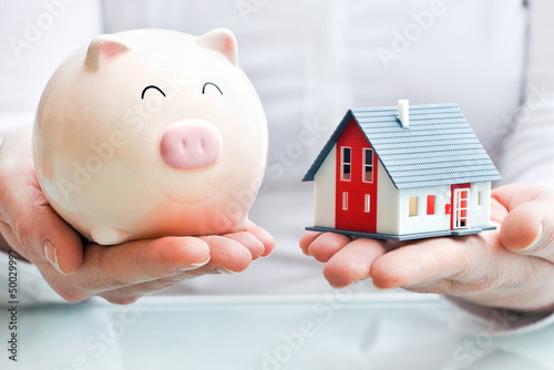 Hands holding a  piggy bank and a house model
