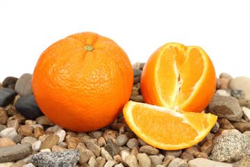 Pomarańcza w całości i pokrojona na kamieniach.