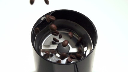 Coffee beans pouring in coffee mill slow motion