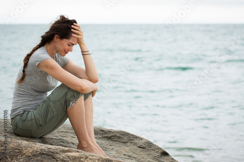 Upset crying woman by the ocean - 50031705