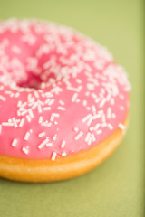 Pink donut on green background