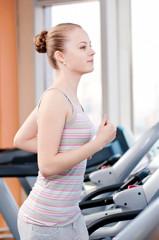 Woman at gym exercising. Run on machine