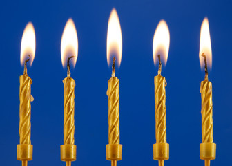 Five golden burning candles on blue background