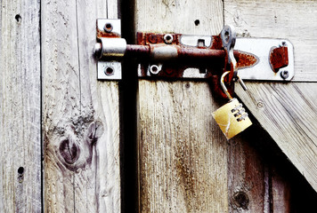 rusty old padlock on wooden gate