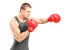Male boxer punching with red boxing gloves