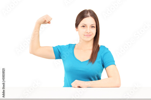 A young smiling woman showing her bicep muscle