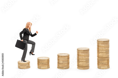Businesswoman with a briefcase walking over piles of coins