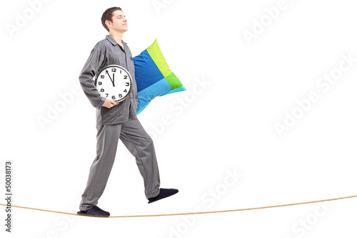 Full length portrait of a young man with pillow and clock sleepw