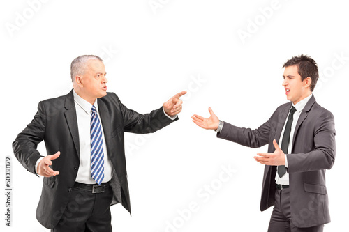 Mature man in a suit having a dispute with a young man in formal