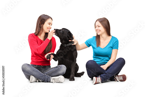 Two female friends sitting and playing with a dog