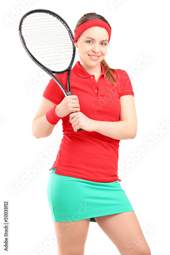 A young female posing with a tennis racket