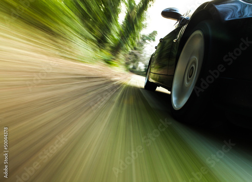 canvas print picture Side view of black car with heavy blurred motion.
