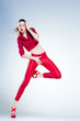 sexy model with slim body dressed in red jumping in the studio