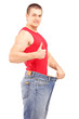 Satisfied weight loss man in a pair of old jeans giving a thumb
