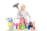 Young smiling woman with a hover and cleaning supplies on a tabl