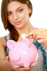 Young beautiful woman standing with piggy bank (money box)