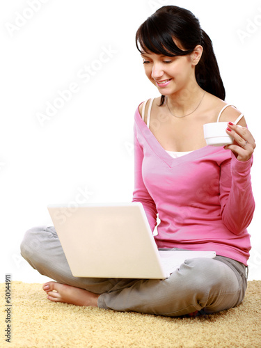 Young woman using laptop  sitting on the floor and holding cup