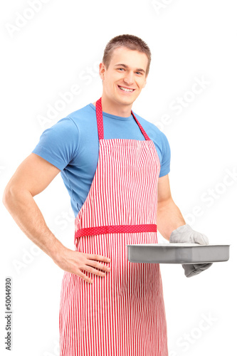 Smiling young man in an apron holding a baking tray