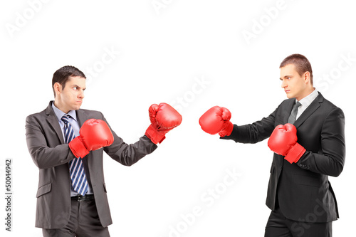 Two young businessmen with boxing gloves having a fight