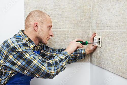 Electrician installing wall outlets