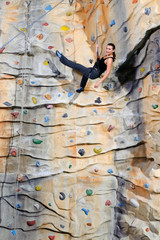 woman on rock wall in sport center