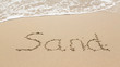 Drawing in beach by ocean of Sand word