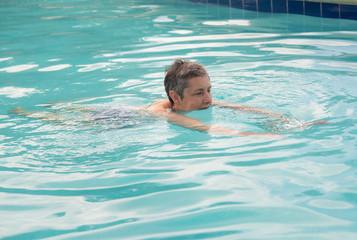 Senior lady swimming in pool