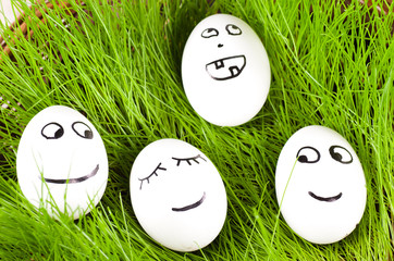 group of  Funny crazy  smiling  eggs in  basket with grass.