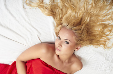 beautiful blond woman with curly hairs lying on bed