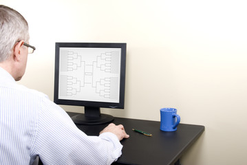March Madness Man at Computer in Shirt Completing Bracket