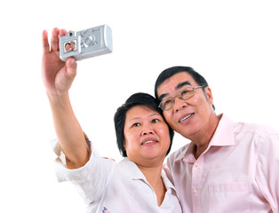 Asian senior couple self photographing