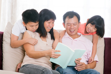 Parents and children reading books at home.