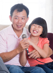 Happy Asian family singing karaoke