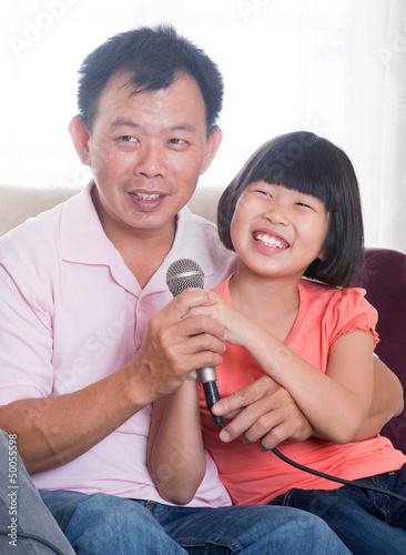 Happy Asian family singing karaoke