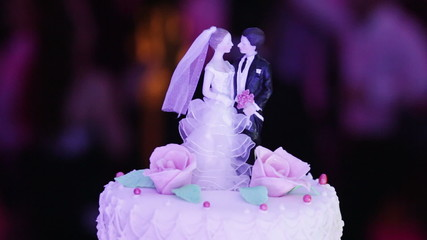 Figures newlyweds on background of dancing people