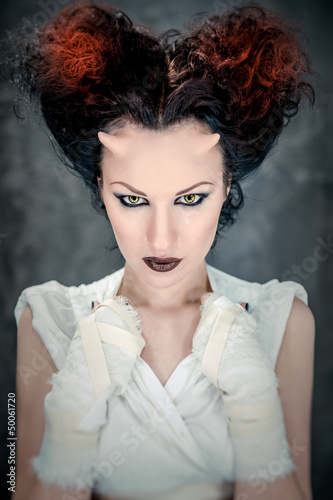 Portrait of beautiful horned woman with bright make-up
