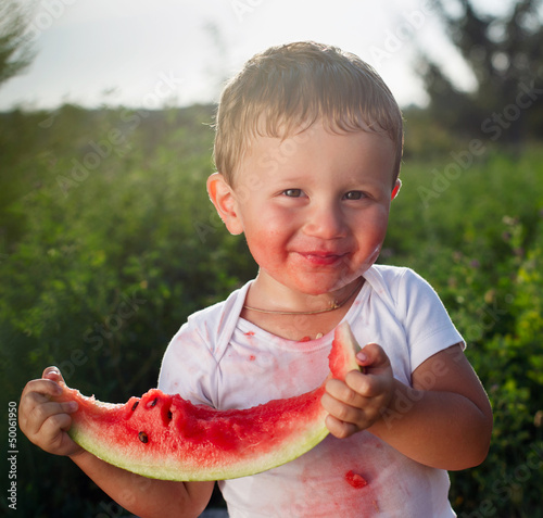 little baby eating watermelon outdoors
