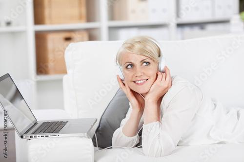 lächelnde frau hört musik mit ihrem laptop