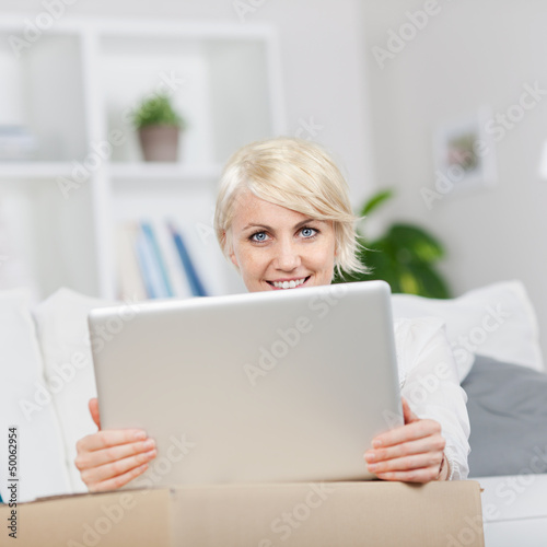 junge frau stellt laptop auf umzugskarton