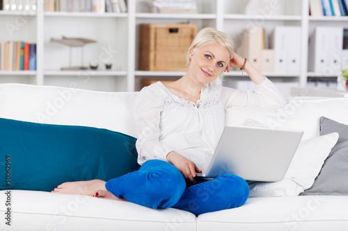 entspannte frau sitzt mit laptop auf dem sofa