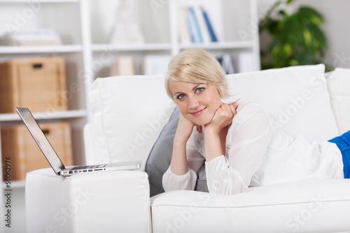 frau liegt mit ihrem laptop auf dem sofa