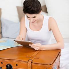 frau plant ihre reise am tablet-pc