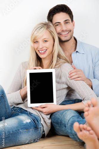 lächelndes paar zeigt tablet-pc