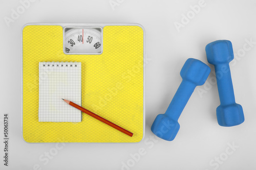 Scales, a notebook with a pencil and a dumbbell. Sports Concept