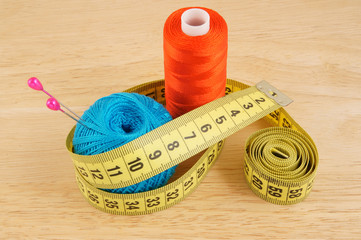 Yellow measuring tape and threads on wooden background