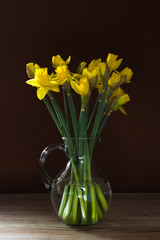 Lent lily daffodil in a glass vase on old wooden table